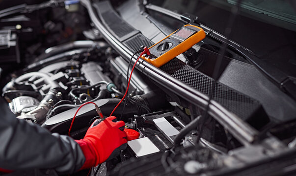 Mechanic checking voltage of car battery