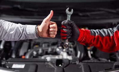 Fototapeta Anonymous man approving job of auto mechanic in workshop obraz