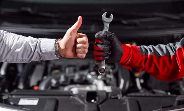 Anonymous man approving job of auto mechanic in workshop