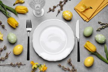 Festive Easter table setting with eggs on grey background, flat lay