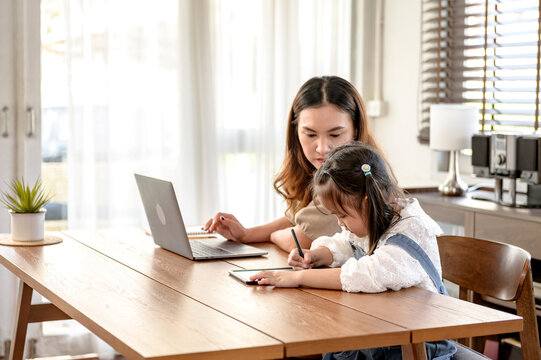 Mom working and teaching daughter for online learning at home. Family togetherness lifestyle and new normal after Covid-19.