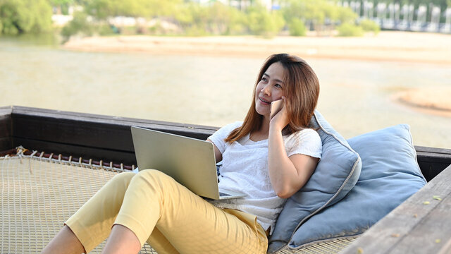 Asian businesswoman working online at the beach. Freelancer using technology for work everywhere. Woman talking with customer with mobile phone.