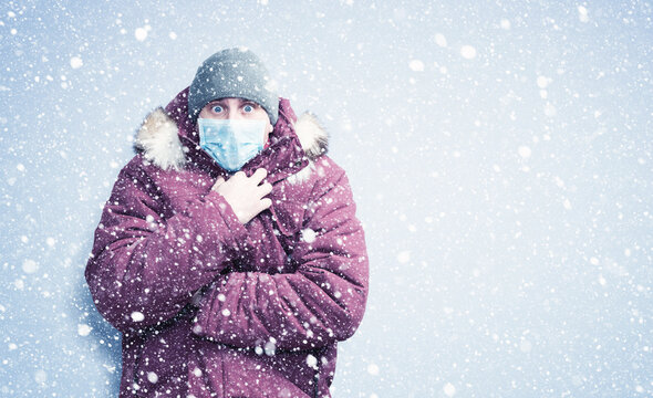 Frozen man in red winter clothes on his face wearing a respirator mask to protect against the virus covid, snow around