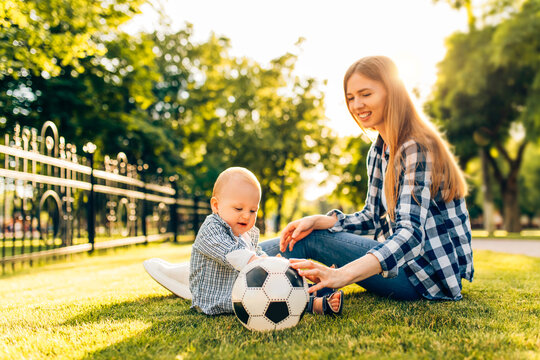 Little child with mom playing with soccer ball on the lawn in the park