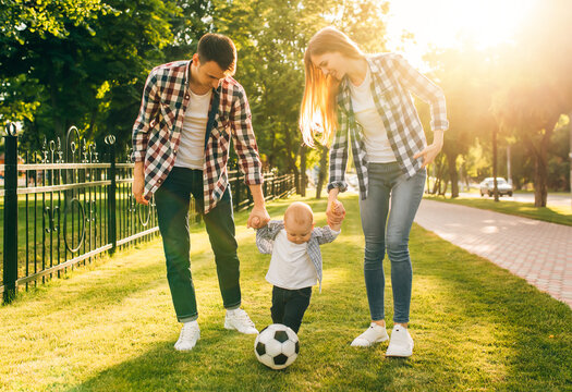 Young happy family holding hands are walking in the park together with a ball