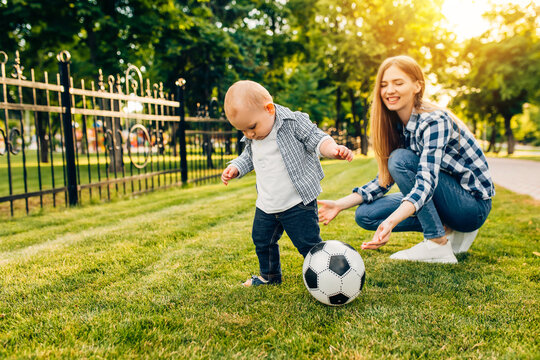 Happy young mom and her little son play soccer together outdoors