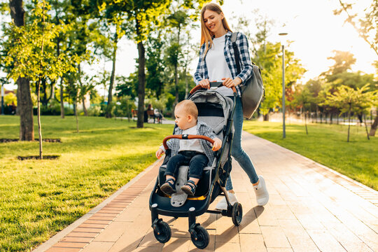 young mother walks with a little toddler in a stroller in the summer on nature