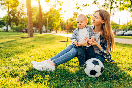 Happy family, mom and her little son are playing soccer ball in the park