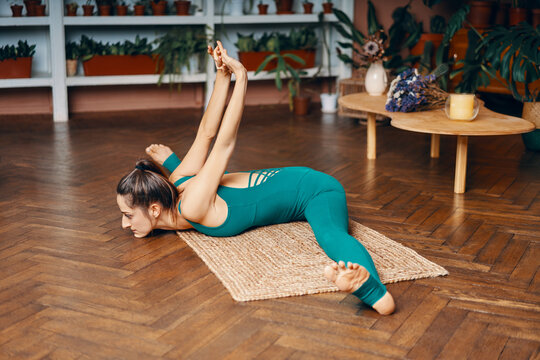 Young slim woman practicing yoga at home doing wide angle seated forward bend pose