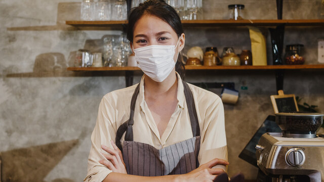 Portrait young Asia girl waitress wear medical face mask feeling happy smile waiting for clients after lockdown at urban cafe. Owner small business, food and drink, business reopen again concept.