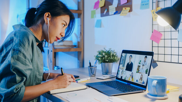Asia businesswoman using laptop talk to colleagues about plan in video call meeting at living room. Working from house overload at night, remotely work, social distancing, quarantine for coronavirus.