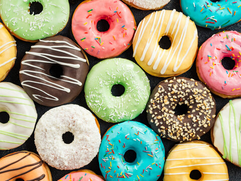 Donuts pattern. Top view of assorted glazed donuts. Colorful donuts with icing as background with copy space. Various colorful glazed doughnuts with sprinkles.