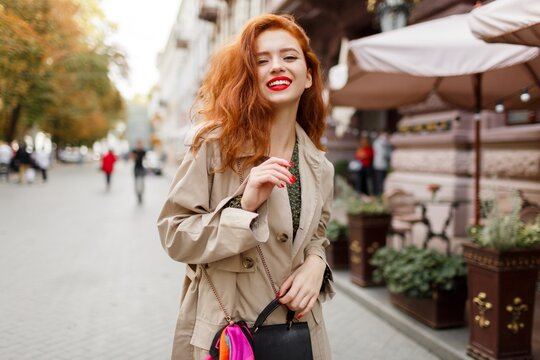 Romantic woman with red hairs and bright make up walking on the street. Wearing beige coat and green dress.