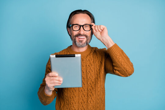 Photo portrait of happy smiling businessman browsing internet tablet wearing glasses isolated on vivid blue color background