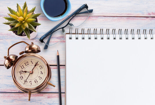 Retro alarm clock,blank notebook,glasses,cup of coffee and flower on a wooden table. Photo in retro color image style.