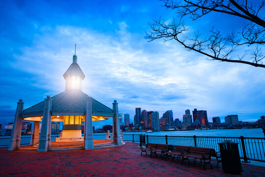 East Boston Piers Park Gazebo with lighthouse light in the evening over downtown panorama
