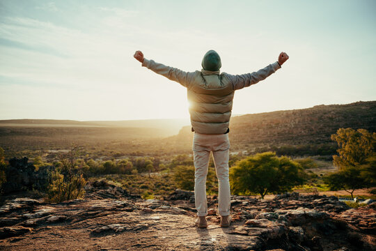 Caucasian male free spirit embracing sunset with arms wide while camping in wilderness