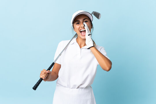 Young hispanic golfer woman over isolated blue wall shouting with mouth wide open