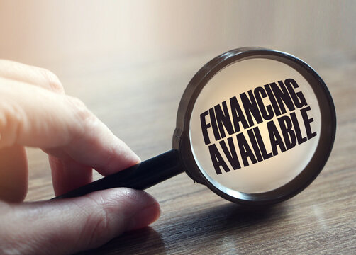 Text Financial available is written under magnifying glass in the hand on the table. Business concept