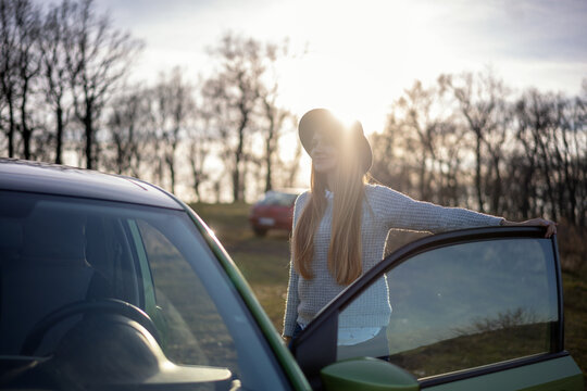 Beautiful young woman wearing hat traveling by car in the countryside on the background of forest and sunset, local travel adventure concept