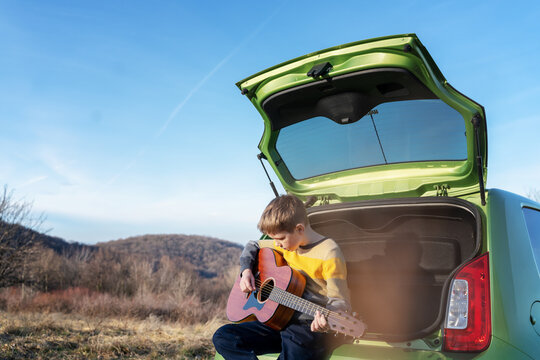 Boy 10 years old playing guitar while sitting on the hood of car during a family car trip