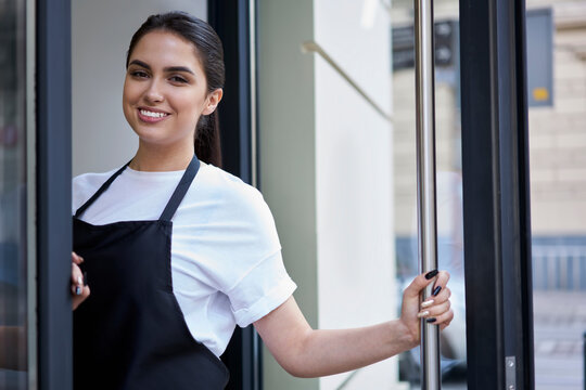 Half length portrait of smiling brunette waitress of coffee shop standing at entrance meeting visitors in morning, hospitable woman owner of cafeteria enjoying work and small business entrepreneurship