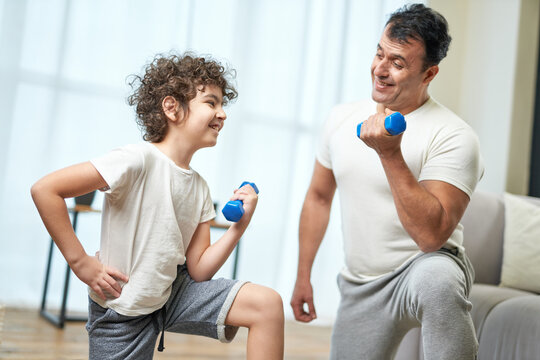 Shaping bodies. Sportive latin middle aged father teaching his son exercising with dumbbells while spending time together at home