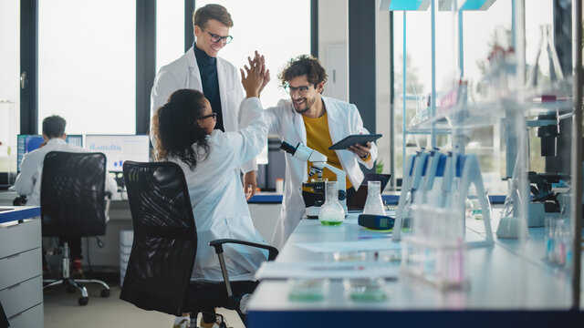 Medical Science Laboratory: Beautiful Black Scientist Discovers New Drug Compound and Celebrate it with High Five. Happy Young Specialists, Doing Innovative Experiments in Advanced Laboratory.