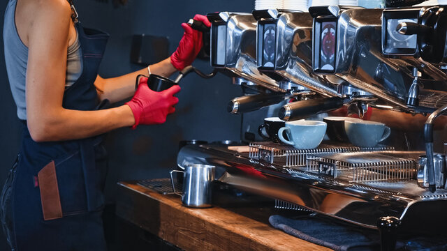 cropped view of barista in latex gloves holding pitcher near steam wand
