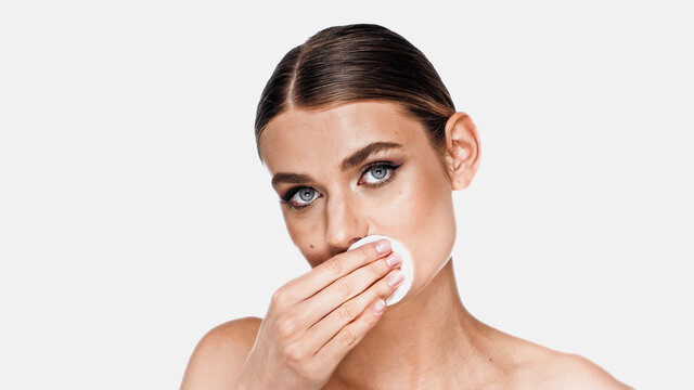 Young woman removing makeup on lips with cotton pad isolated on white