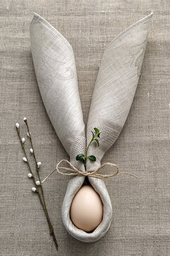 Decorative Bunny Ears from napkin with egg on natural cotton tablecloth to Celebrate Easter, DIY, flat lay