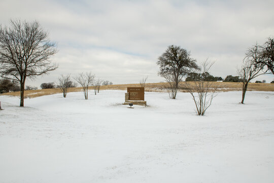 Winfrey Point Sign surrounded by snow and ice on the ground after winter storms in Dallas Texas near White Rock Lake