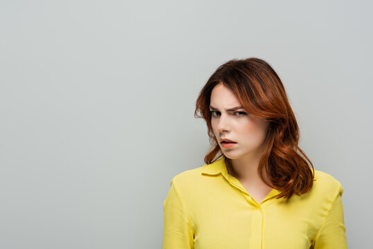 distrustful woman in yellow blouse looking at camera isolated on grey
