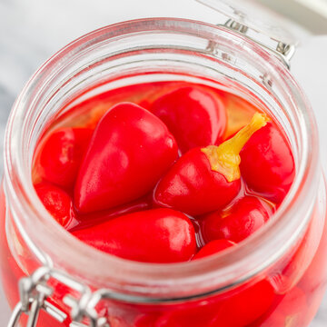 Red hot chili pepper. Piri piri close-up. Pickled peppers in a glass jar on a marble table. A gourmet snack for meat and poultry. (Capsicum chinense). Selective Focus