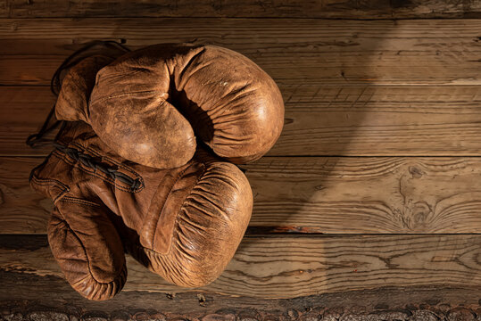 Antique boxing gloves on rustic wood base