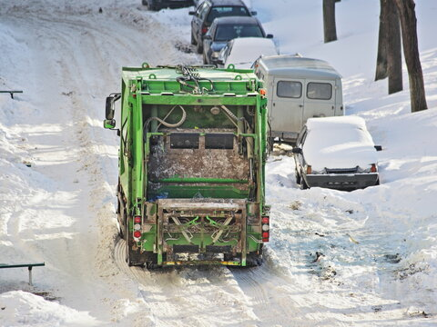 A green garbage truck drives through a snow-covered city courtyard road near parked cars on a winter day after a heavy snowfall
