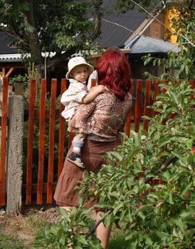 Frau mit Kind am Gartenzaun