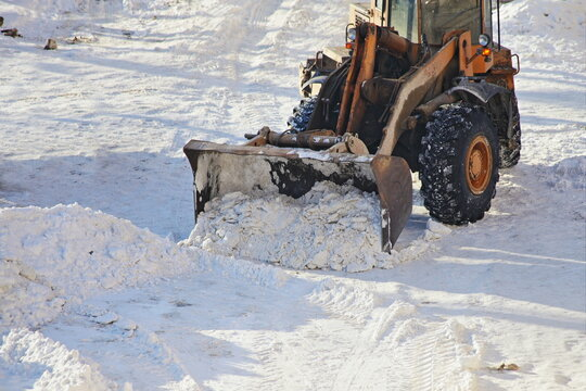 One yellow heavy wheeled tractor bulldozer removes a snow with scraper shovel blade snowplow on highway road after heavy snowfall at Sunny winter day, top front view close-up