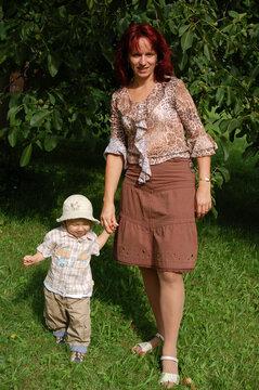 Frau mit Kind an der Hand im Garten