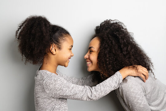 African american mother with her daughter looking and smiling at each other.