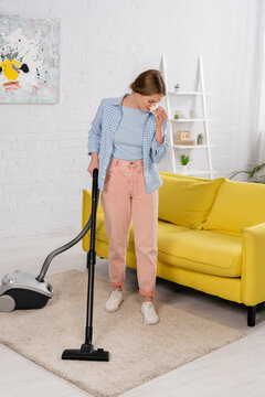Woman with allergy on dust cleaning carpet with vacuum cleaner