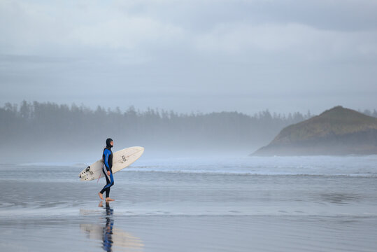 Man in wetsuit walking with a surfboard, Long Beach, Pacific Rim National Park.