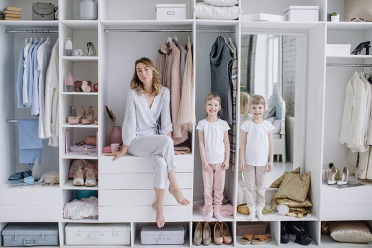 Female wardrobe. Stylish mother, cute twin daughters wearing comfortable home clothes posing in closet. Happy motherhood