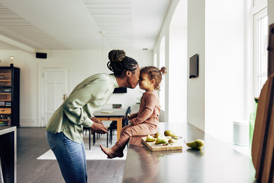 Loving mom and her little girl having a snack at home