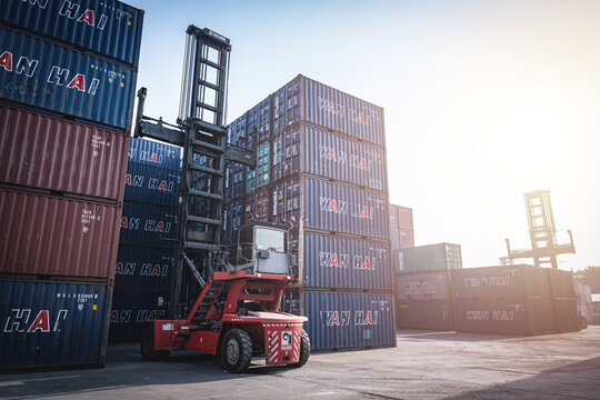 BANGKOK, THAILAND - FEBRUARY 14, 2021: Forklift operating at the shipping yard in the morning. Stack of shipping containers waiting to be exported worldwide.