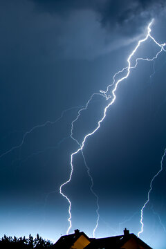 Vertical shot of lightning in the night sky over the village houses
