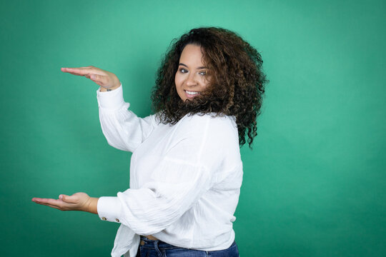 Young african american girl wearing white shirt over green background gesturing with hands showing big and large size sign, measure symbol. Smiling . Measuring concept.
