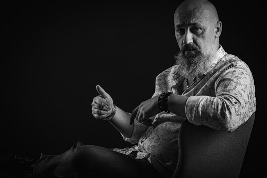 portrait of a serious, bald, bearded man in a T-shirt. With a lush beard looking away, posing on a dark background. Fashion and style. Close up, space for inscription. Black and white photo