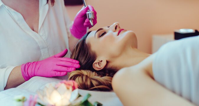 Cosmetologist giving woman a skin treatment with laser technology