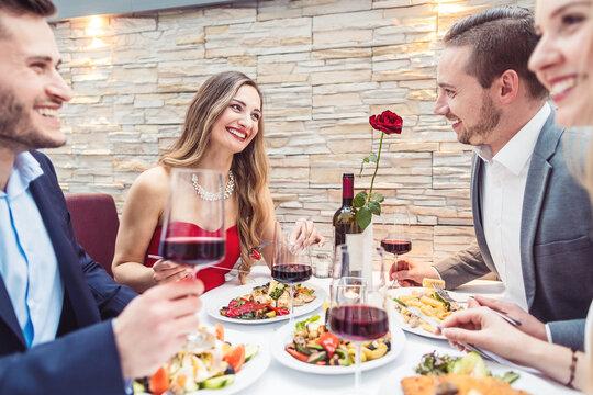 Friends enjoying atmosphere, food, and drink in fancy restaurant
